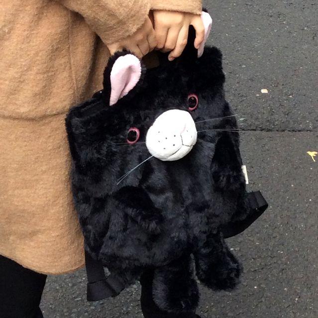 ヌイグルミタイプのリュックにもなるルートート猫2WAYバッグをモデルさんが手で持った所の写真