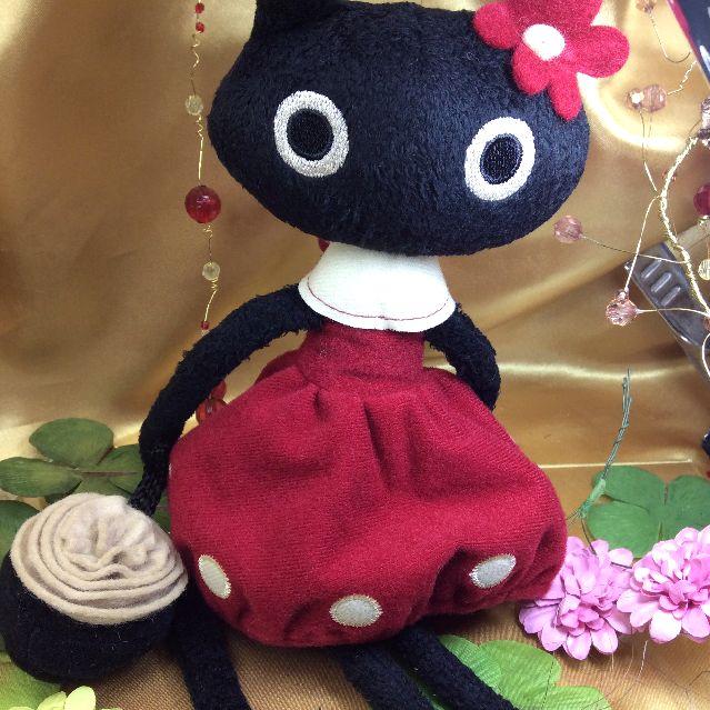 マタノアツコ先生お花のバッグを提げて赤いワンピースを着飾る黒猫メメちゃん縫いぐるみの全体写真