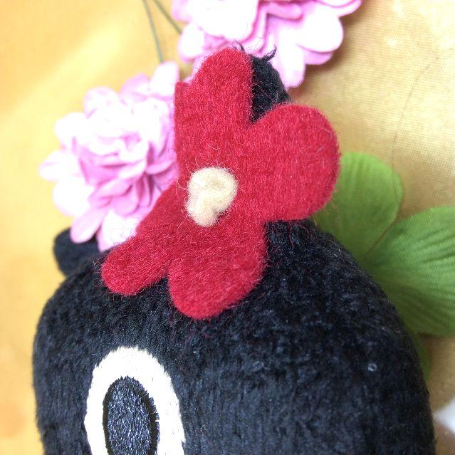 マタノアツコ先生お花のバッグを提げて赤いワンピースを着る黒猫メメちゃん縫いぐるみの頭の花の部分アップ写真
