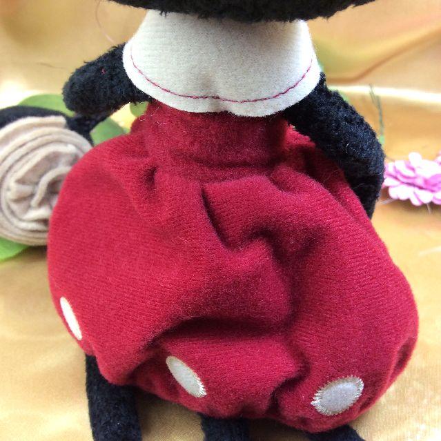 マタノアツコ先生お花のバッグを提げて赤いワンピースを着飾る黒猫メメちゃん縫いぐるみの洋服部分を後ろから写した写真